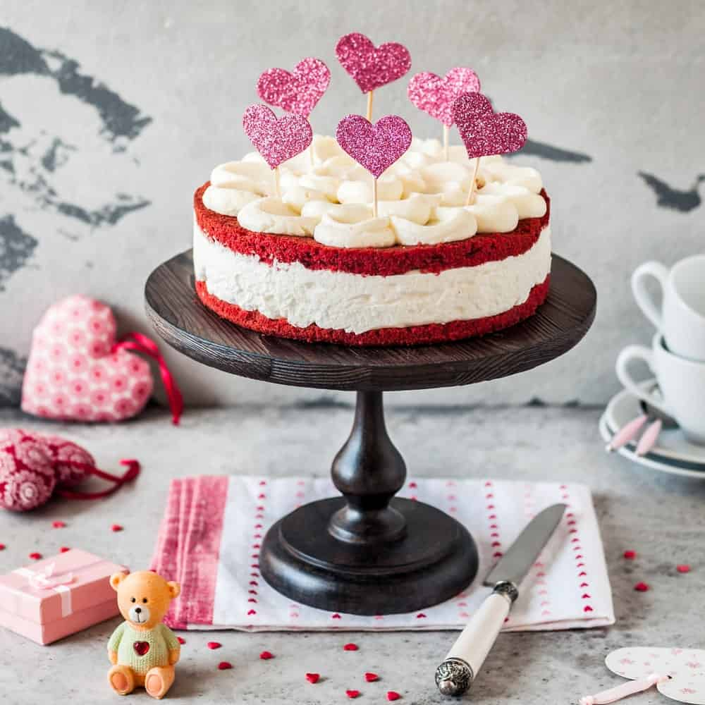 Red velvet cheesecake with heart-shaped cutouts on cake table.