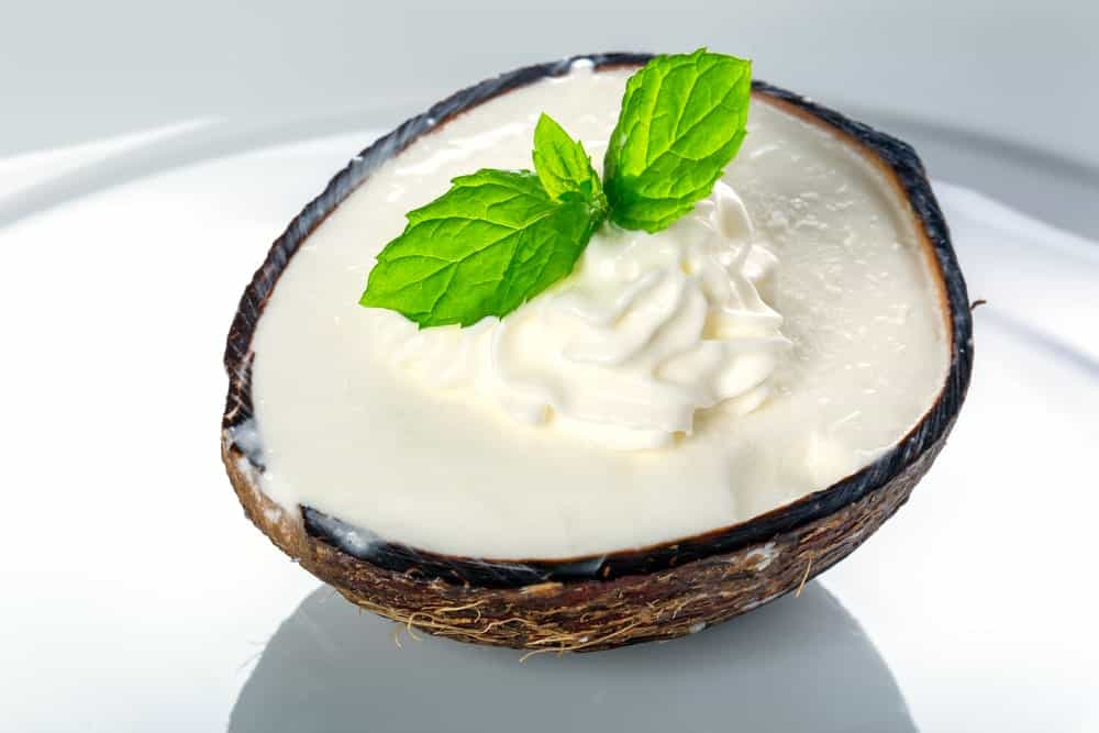 Coconut ice cream with leaves at the center on coconut shell.