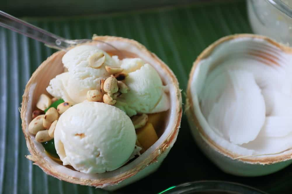Coconut ice milk on coconut shell on banana leaf.