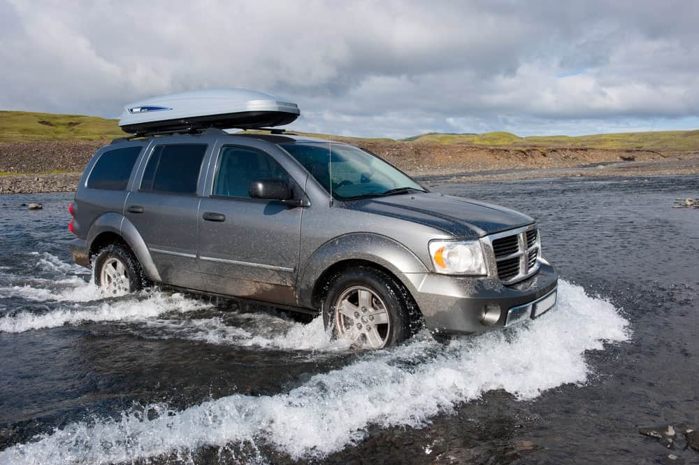 A gray Dodge Journey with hood crosses the water.