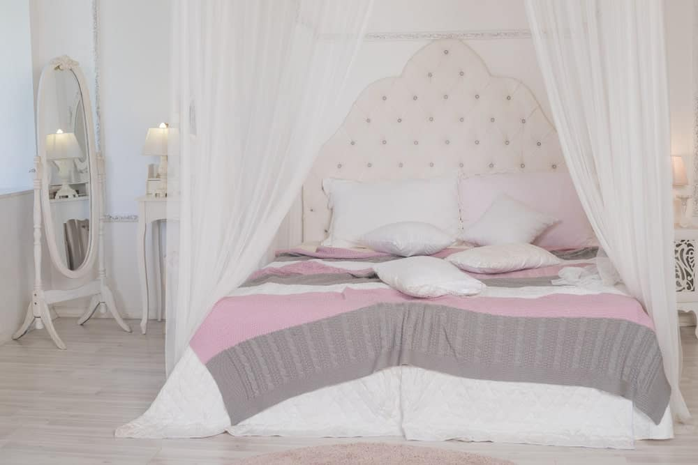 Four poster bed with white canopy drapes, pastel-colored bedroom, and an oval mirror beside the bed.