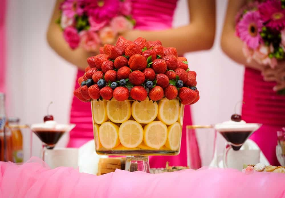 Strawberries, blueberries, and slices of lemons on a cake tray featured on a wedding ceremony.