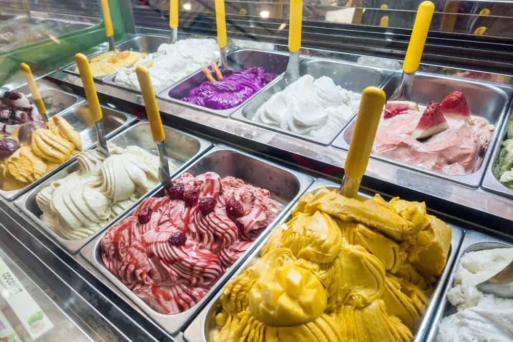 A display of various gelato flavors at a store.
