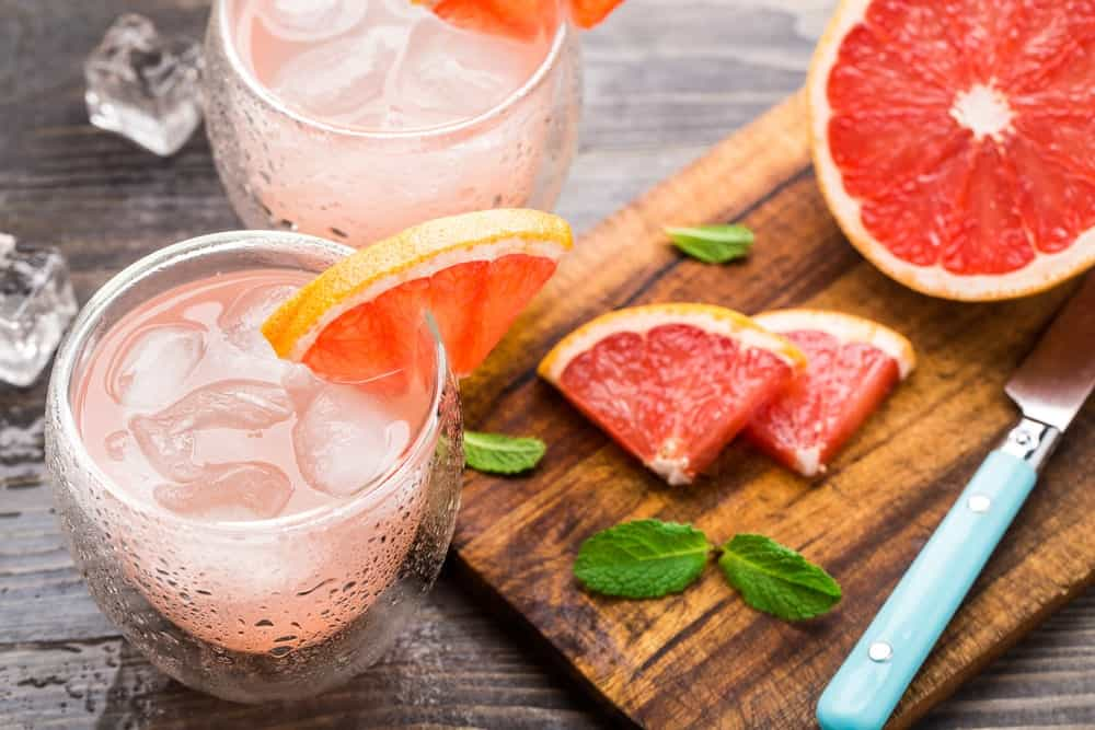 Two glasses of grapefruit cocktail beside a wood chopping board with a knife and slices of grapefruit.