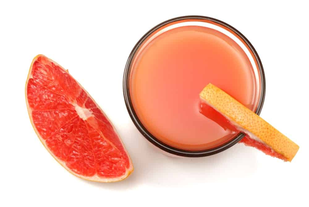 Top view of a grapefruit juice and slices of the fruit.