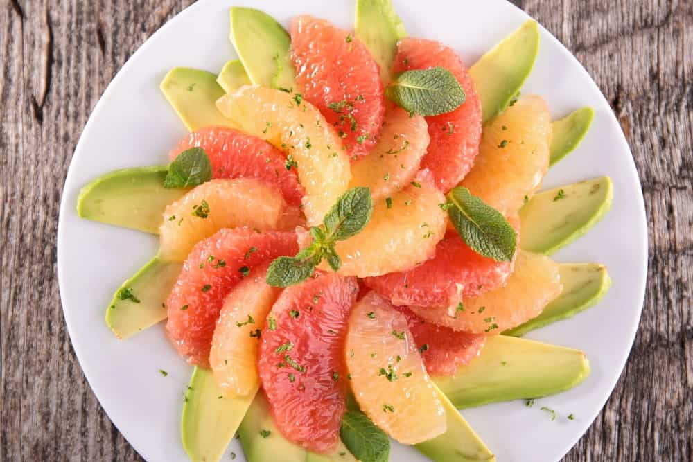 A plate of grapefruit and avocado salad on wooden background.