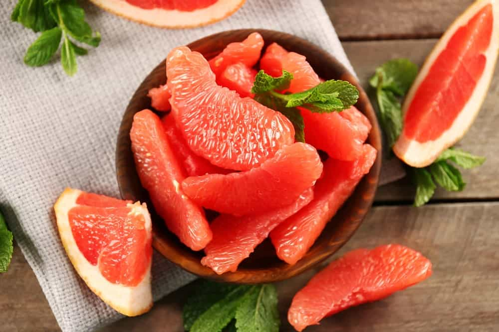 Slices of grapefruit on a wooden bowl and wooden background.
