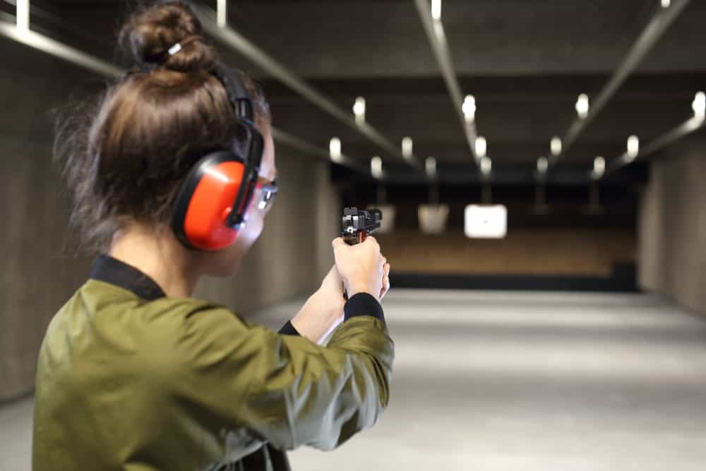 A woman wears a low profile headphone during practice shooting.