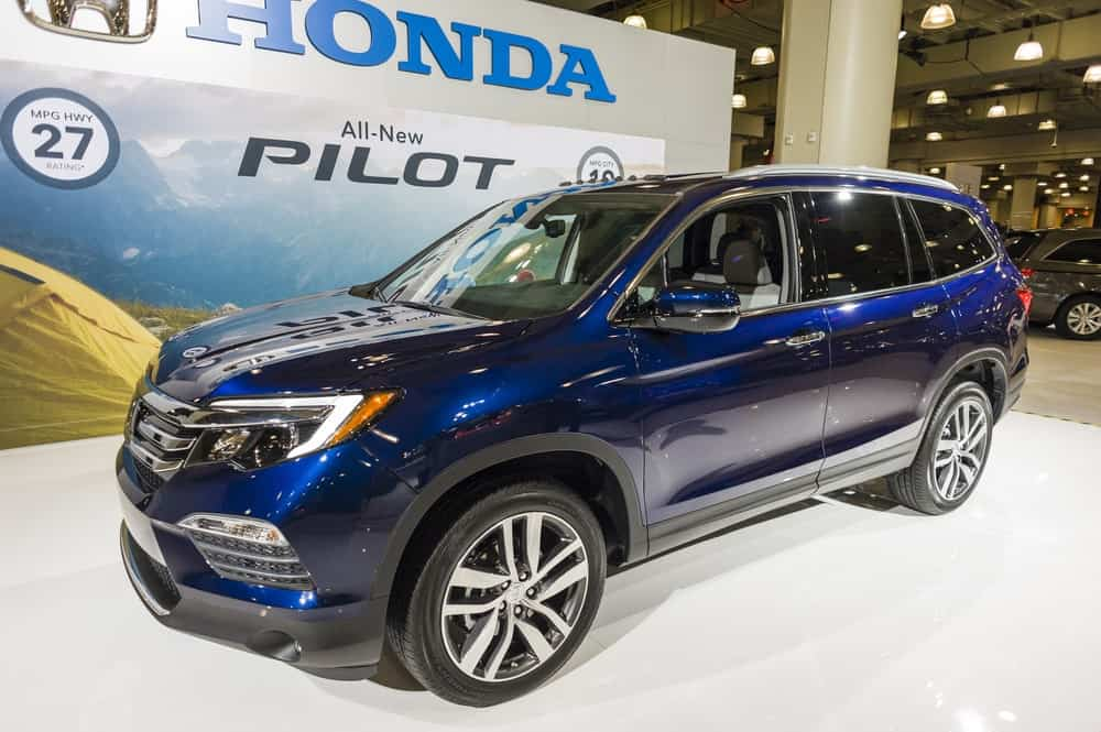Blue Honda Pilot at a showroom.