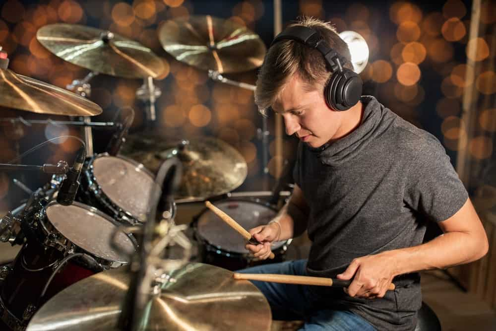 Drummer wearing an isolation headphone while playing on the drums.