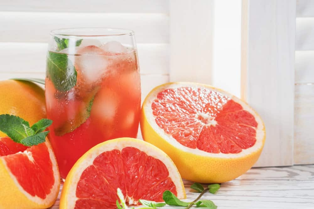 A glass of grapefruit juice surrounded by slices of grapefruits.