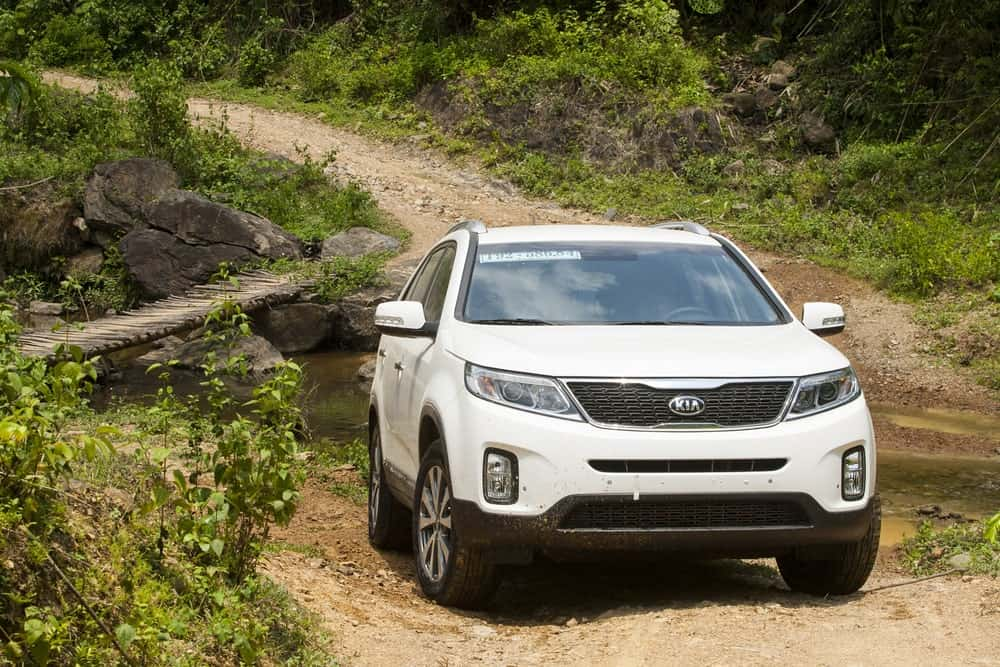 White KIA Sorento on a mountain road test drive.