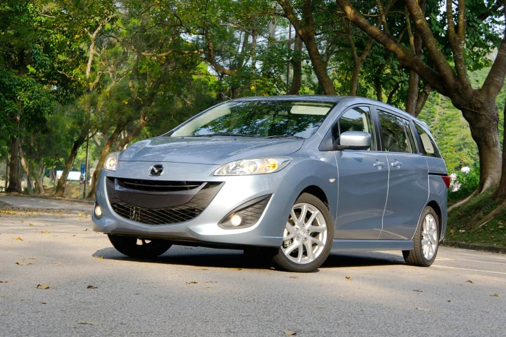 Gray Mazda 5 parked under tree foliage.