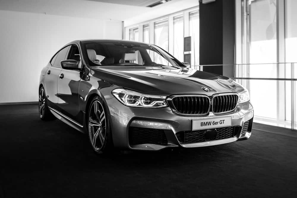 A black midsize BMW is pictured inside a car showroom