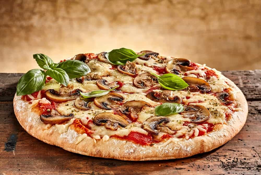 Mushroom pizza on wooden background.