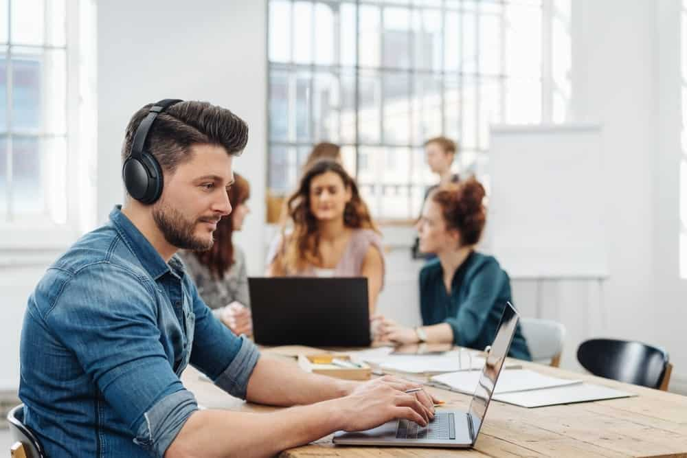 Man wearing a noise cancelling headphones as he works on his laptop while people at the background talk to each other.