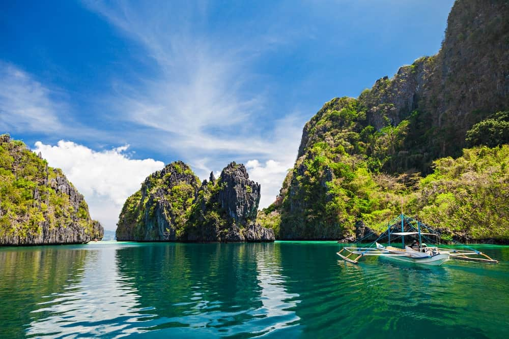 Boat on green waters surrounded by monolithic rock structures in El Nido, Philippines.