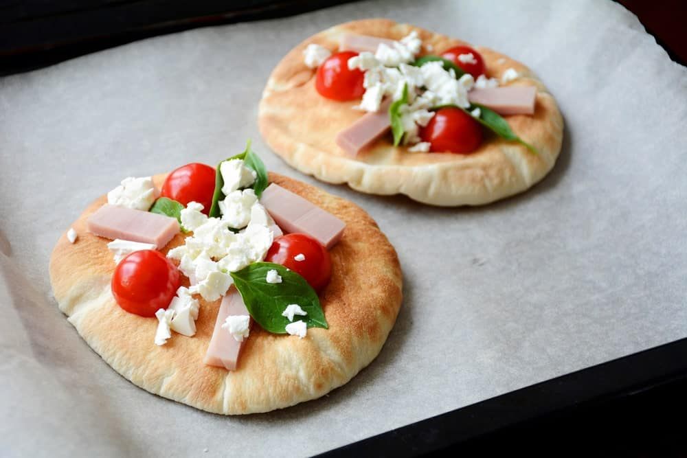Two pita bread pizza on white paper.