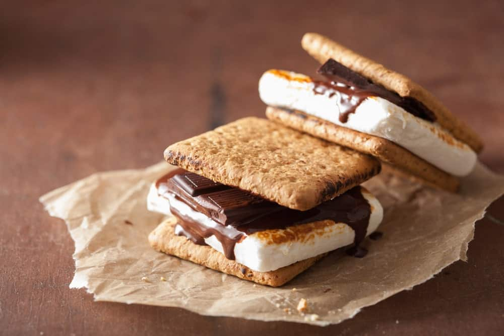 S'mores on a piece of paper and on a wooden background.