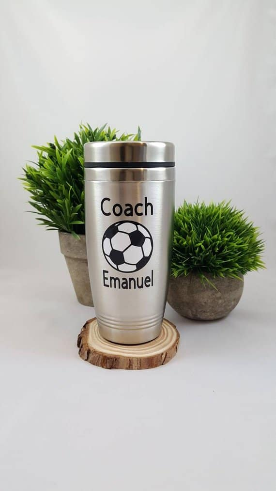 Soccer-themed travel mug on a wooden coaster and in front of two potted plants.