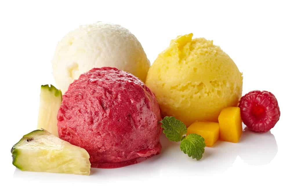Raspberry, mango, and coconut ice cream sorbet surrounded by fruits.