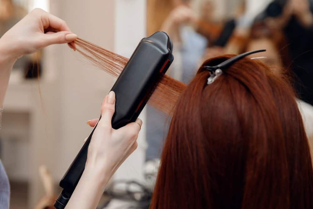 Stylist relaxing a ginger hair woman.