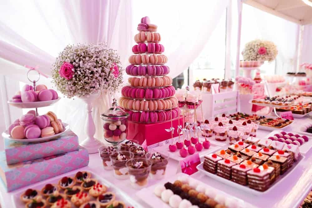 An assortment of pink-colored sweet treats on a wedding ceremony's sweets table.