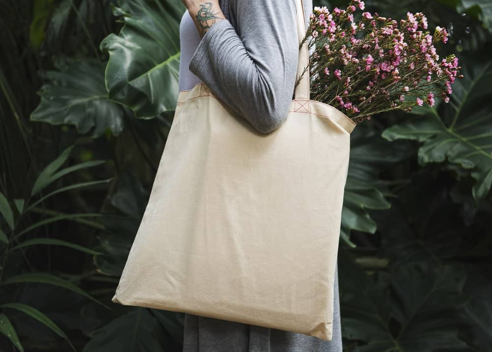 Person wearing a white tote bag with flowers coming out from the bag.