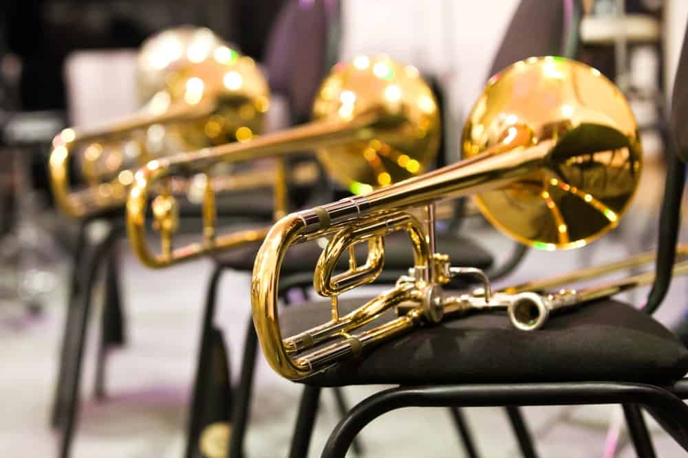 A line of trombones is pictured here as they are displayed on top of cushioned chairs.
