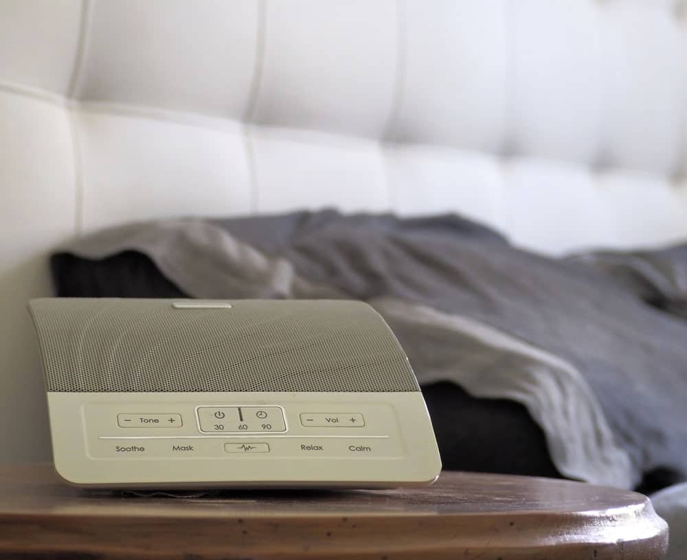 White noise machine on the bedside table.