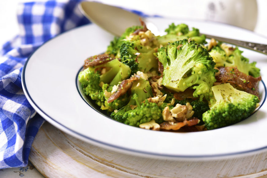 Bowl of cooked broccoli with walnuts