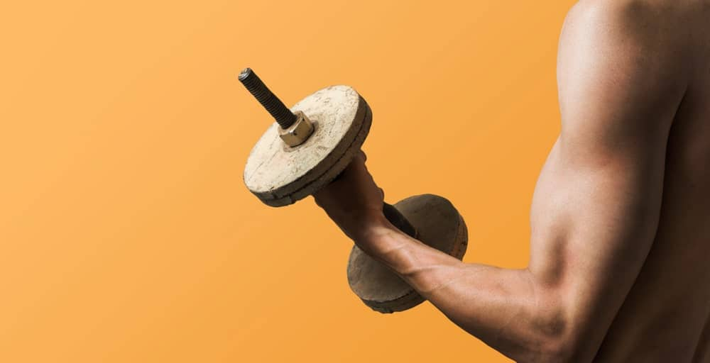 Man working out using a DIY dumbbell.