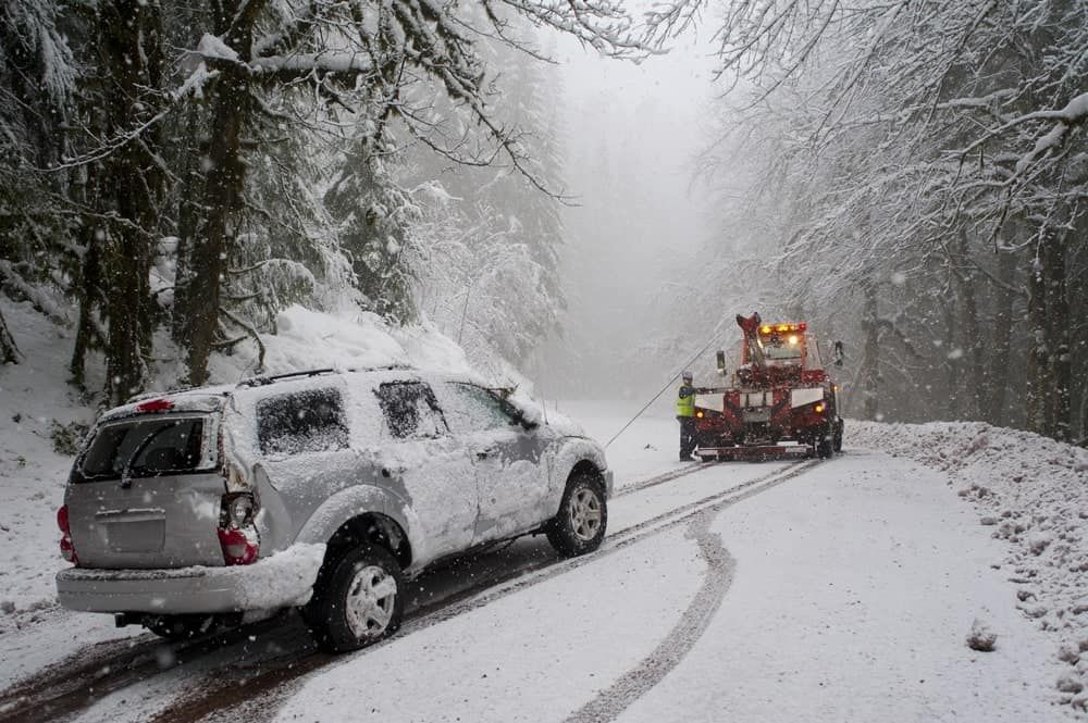 A vehicle being towed after a storm accident in the road.