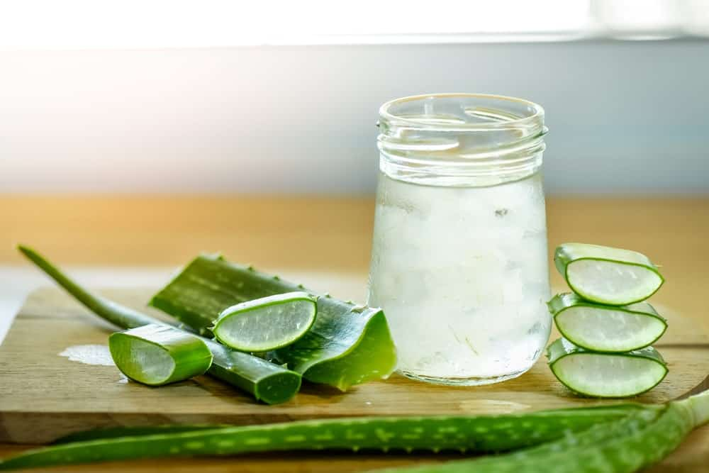 A jar and slices of aloe vera on a wood cutting board.