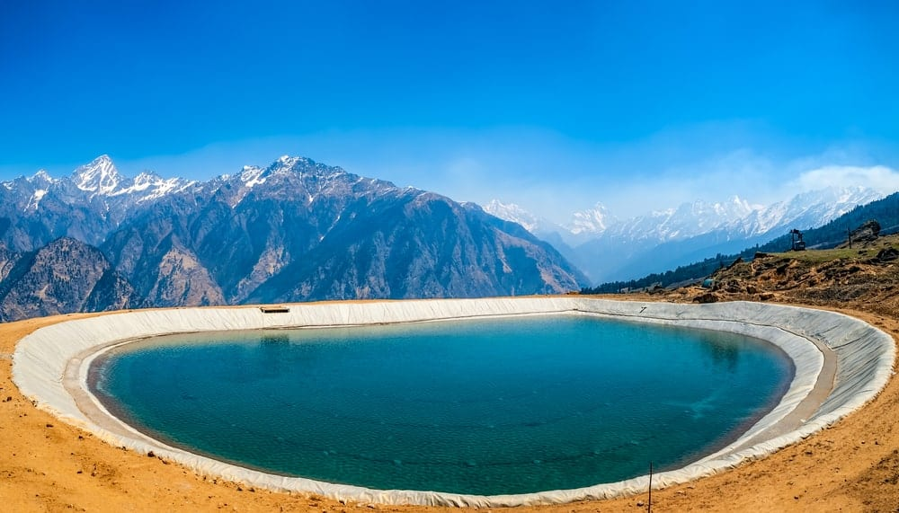 An artificial lake with a view of the Himalayan mountains.
