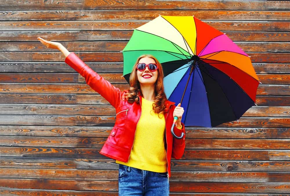 Woman in colorful outfit holding a rainbow-colored umbrella.