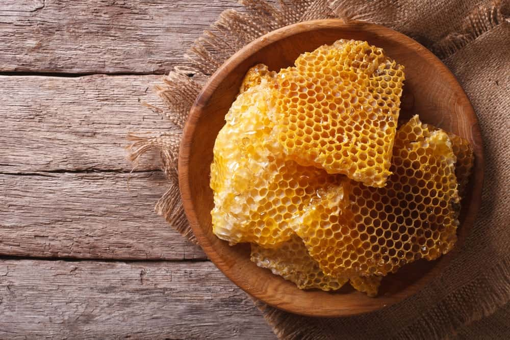 A bowl of beeswax on wooden background.