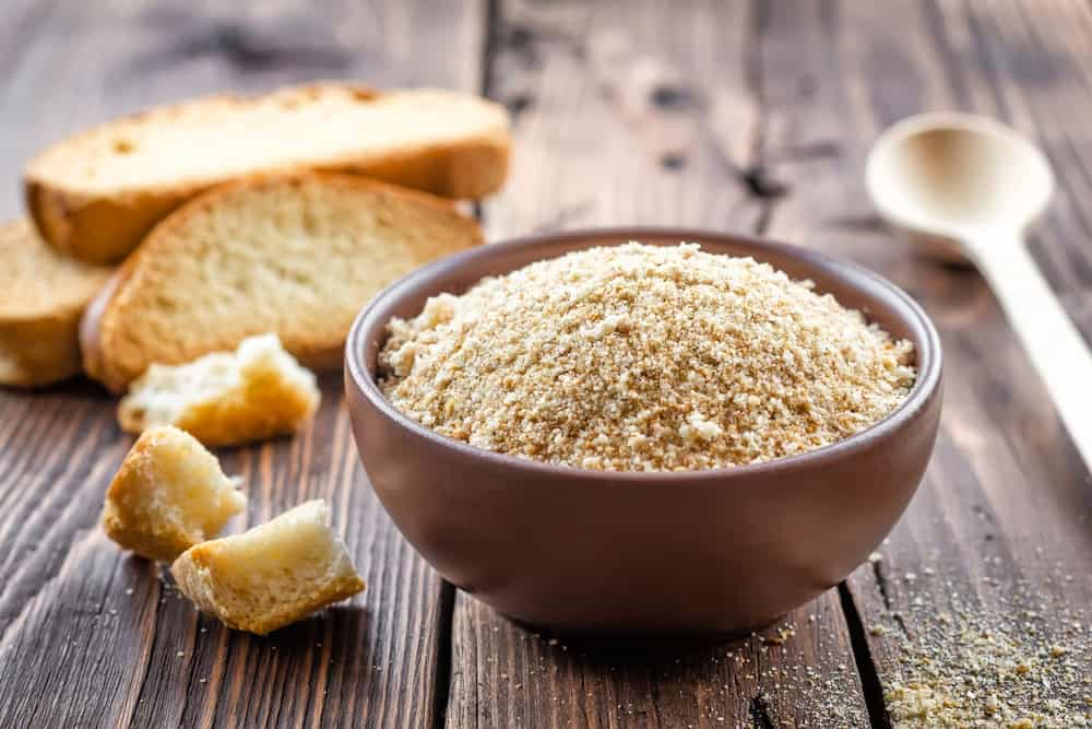 A bowl of breadcrumbs beside slices of bread and a wooden spoon on a wooden surface.
