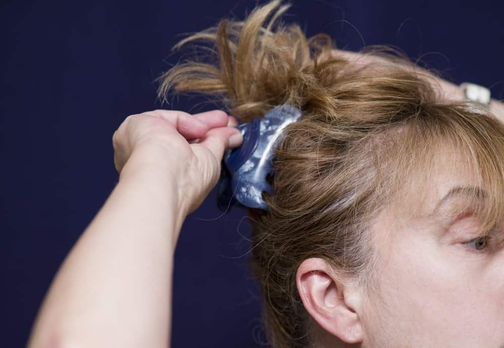 Woman tying her hair up with a hair clip.