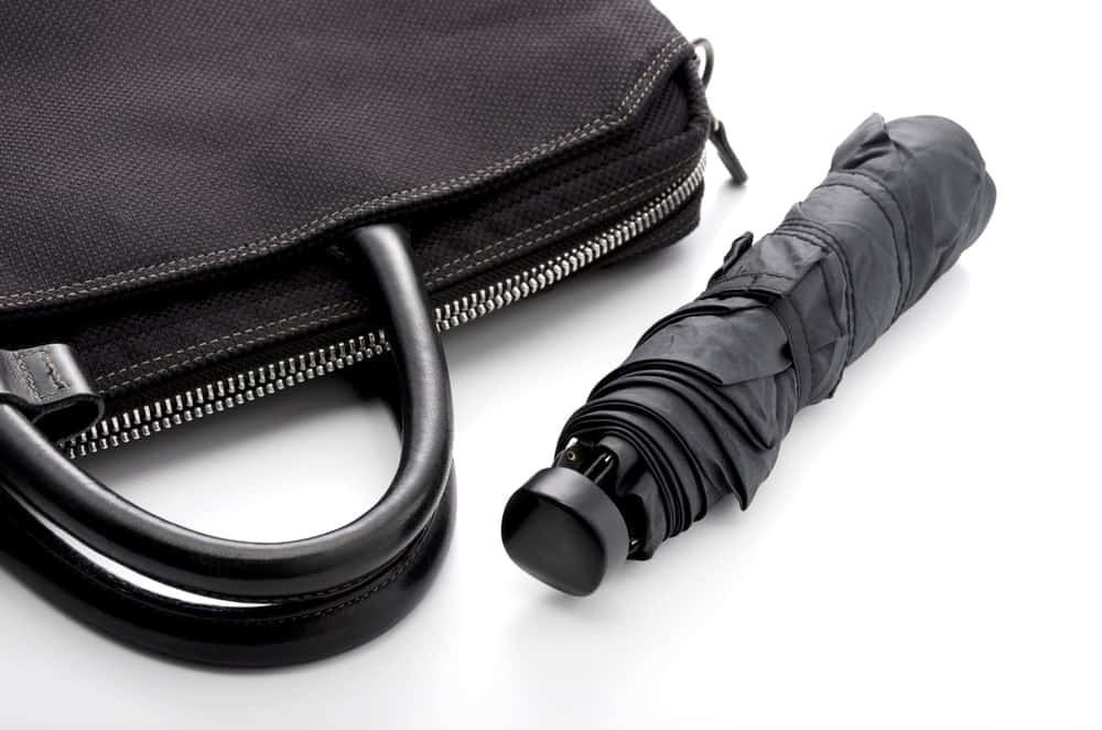 Compact umbrella beside a handbag.