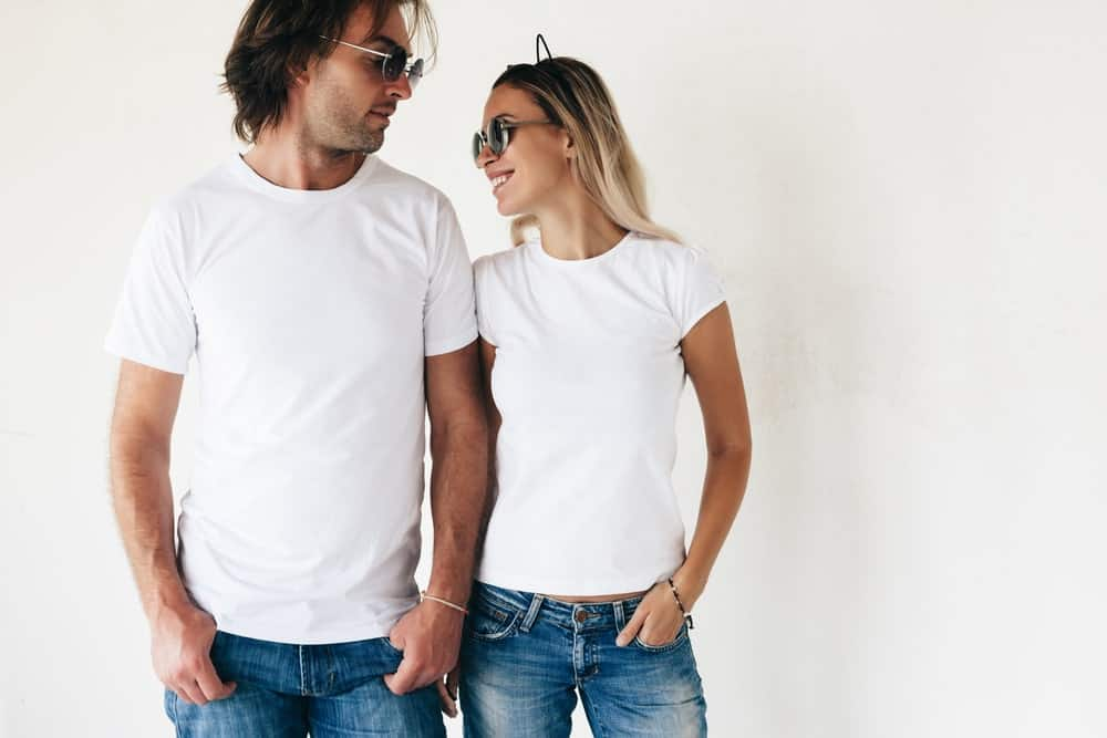 A man and a woman wearing basic white T-shirts and jeans.