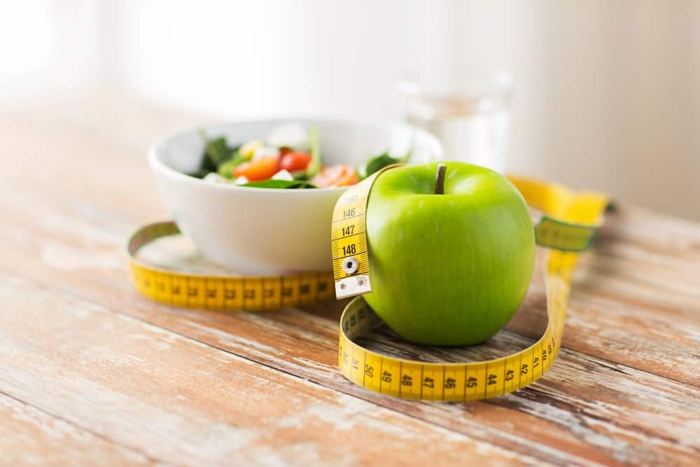 Diet concept with a glass of water, bowl of vegetable salad, green apple, and tape measure on wooden table.