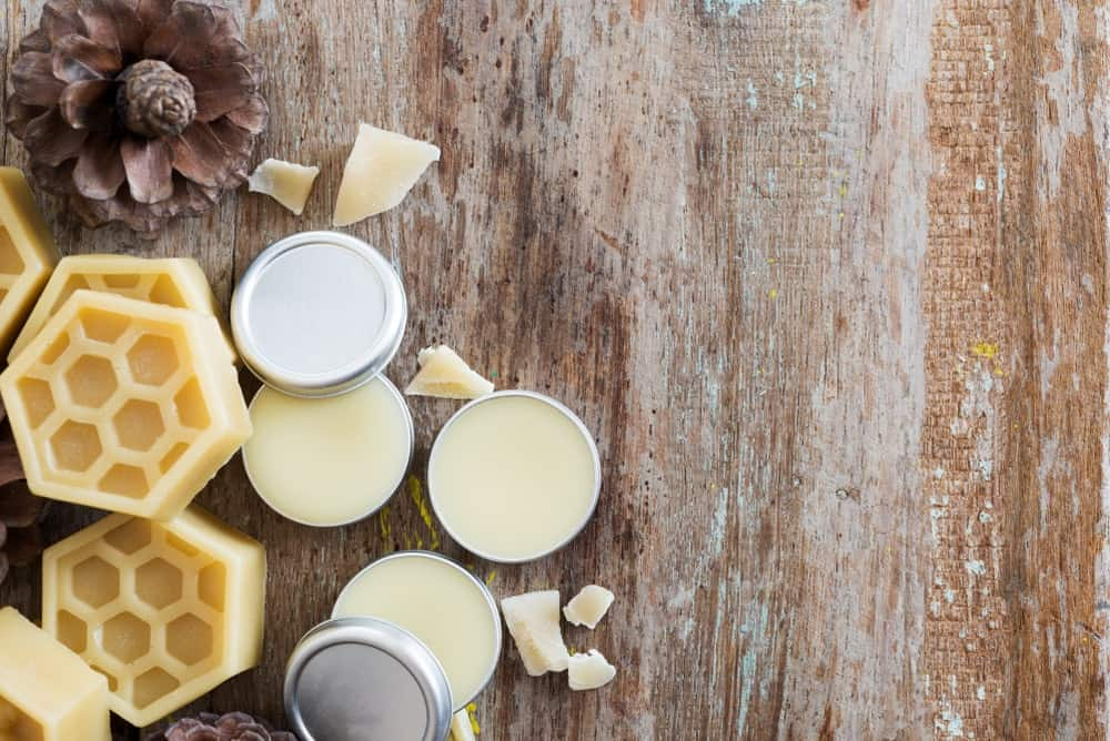 Ingredients for a homemade lip balm such as beeswax pellets and shea butter on wooden background.
