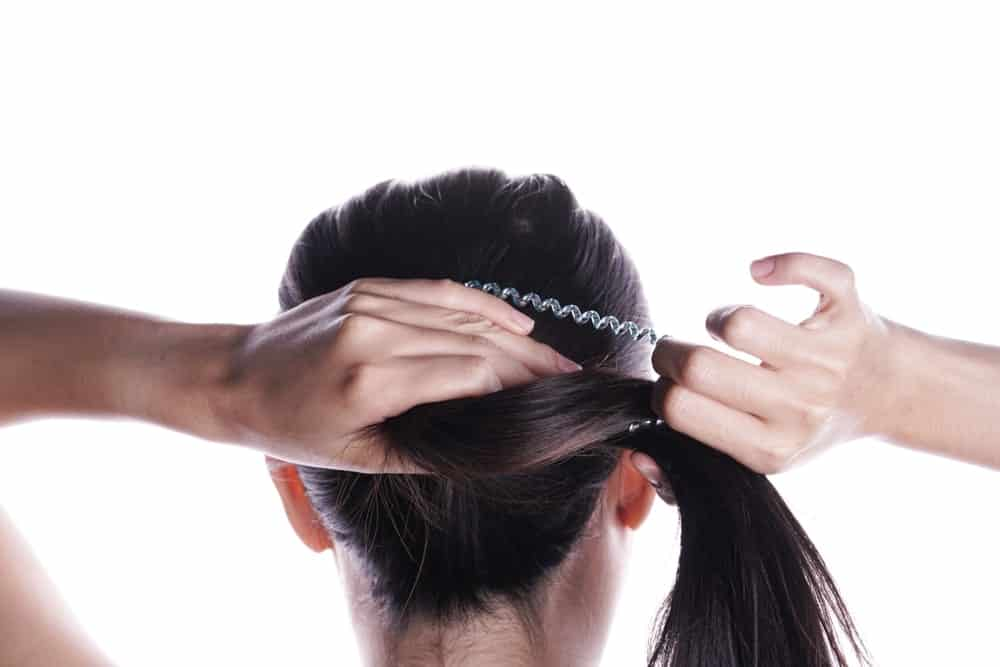 Back view of a woman tying her hair with an elastic tie.