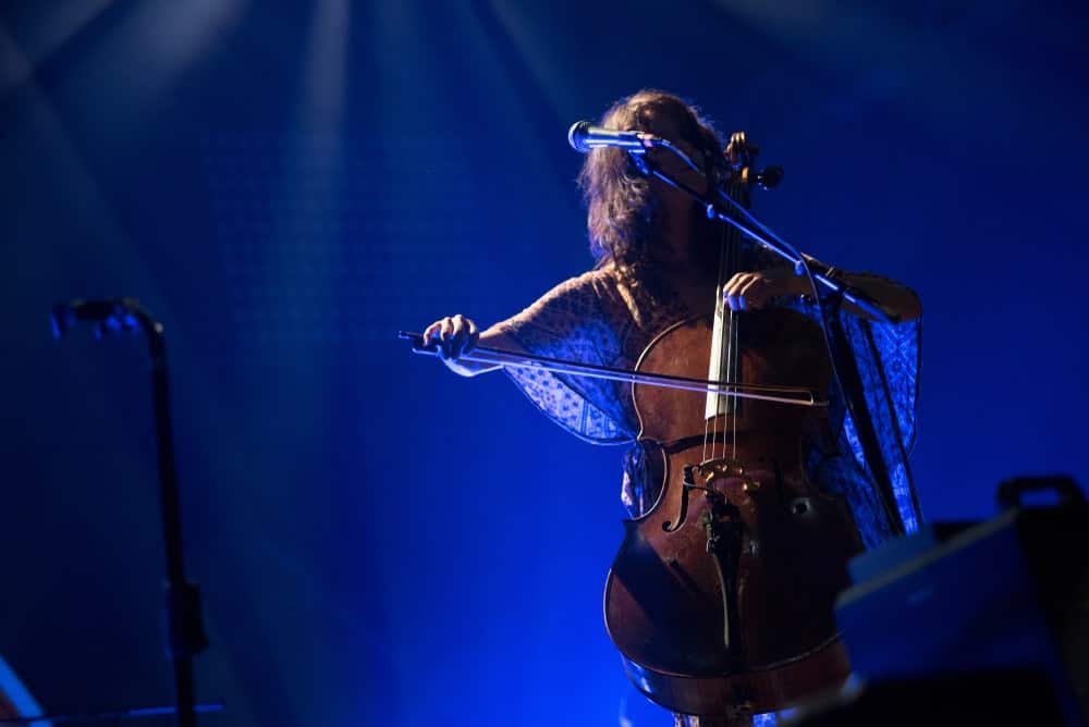 Cellist playing an electric cello on a concert stage.