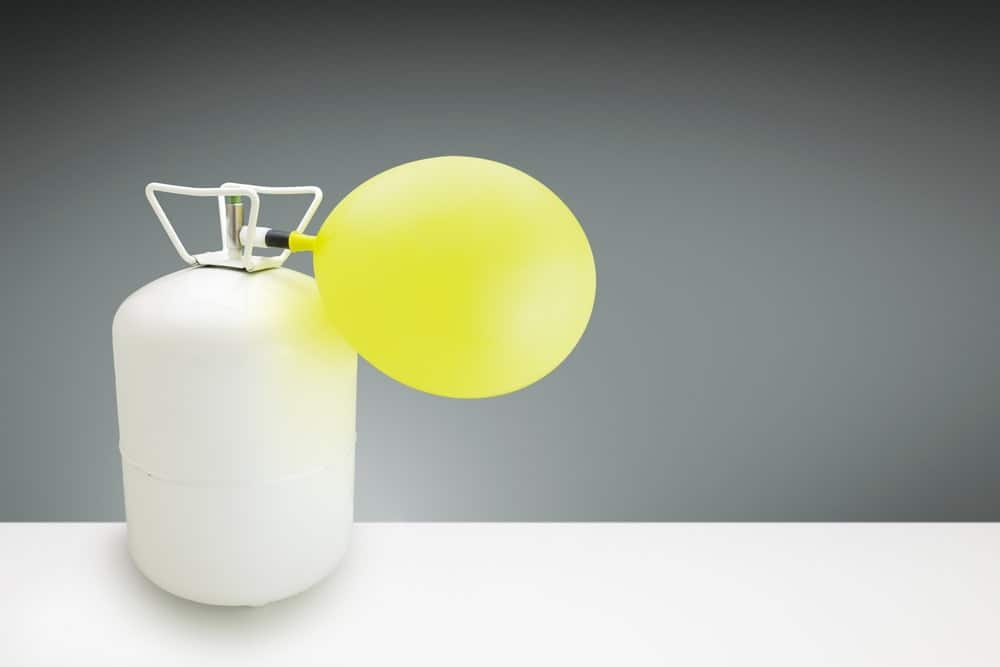 Yellow balloon being filled up by a tank of helium gas.
