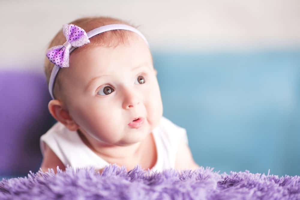 Cute baby wearing a purple ribbon headband.