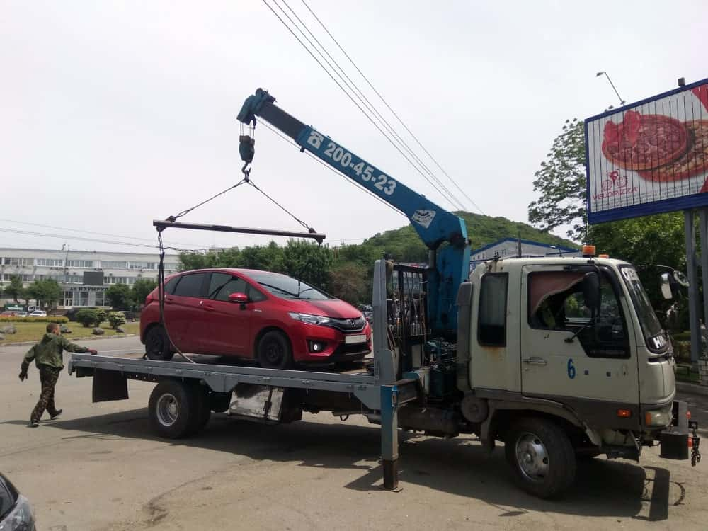 A tow truck moving an improperly parked car.