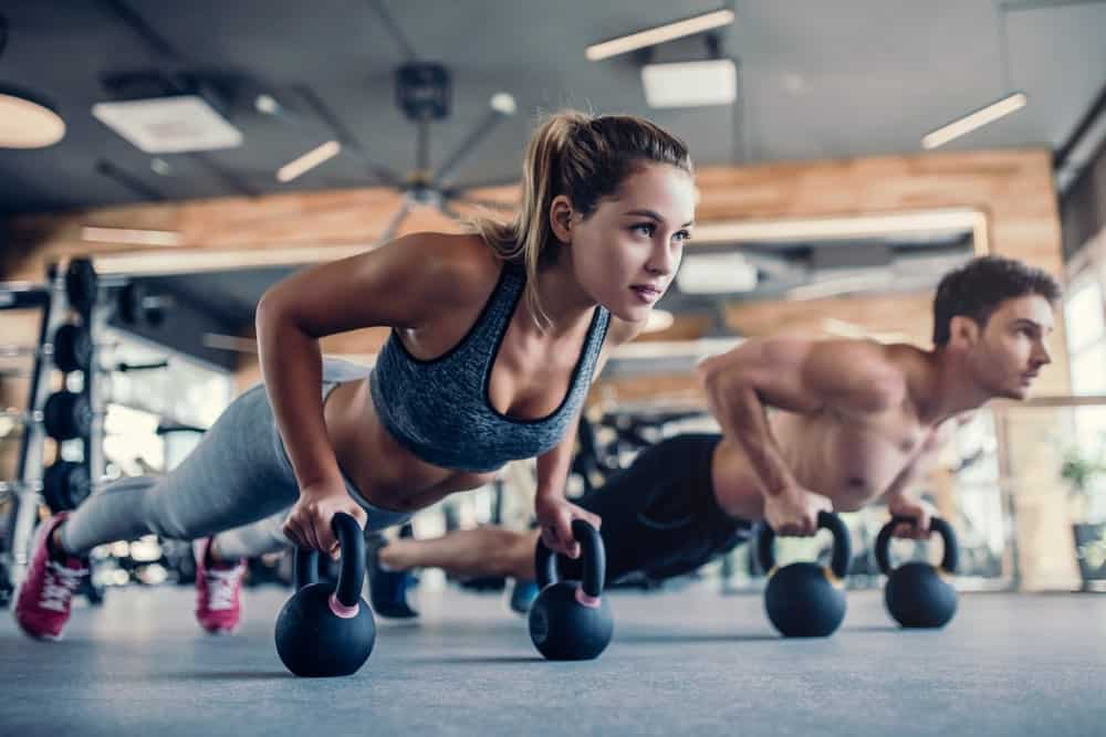 A young woman and a young man working out using kettlebells.