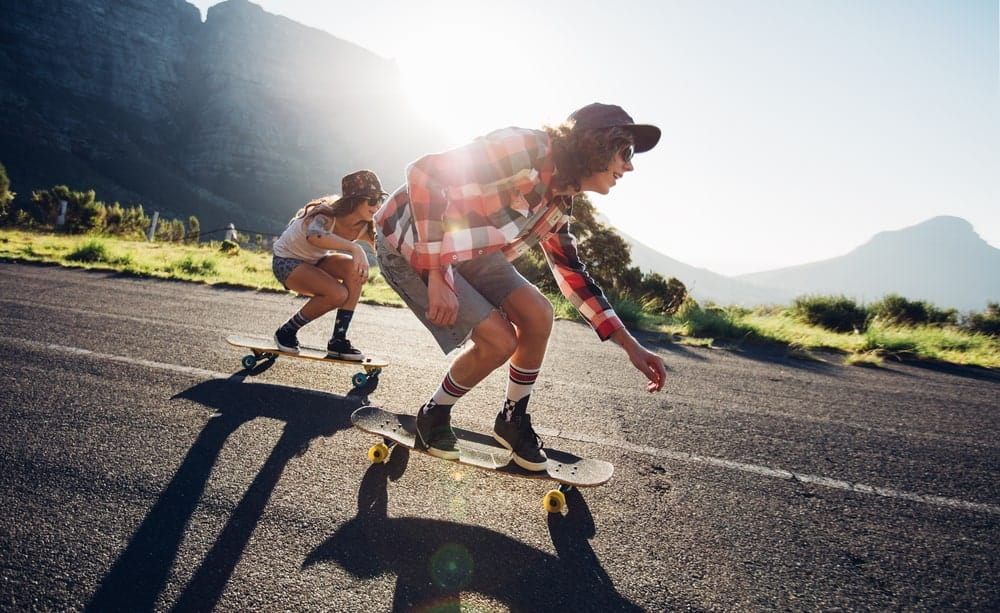 A young man and woman riding longboarding on the road.